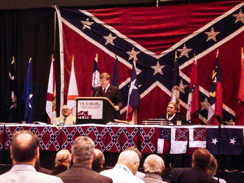 Mississippi Lt. Gov. Tate Reeves stands in front of a large Confederate flag.
